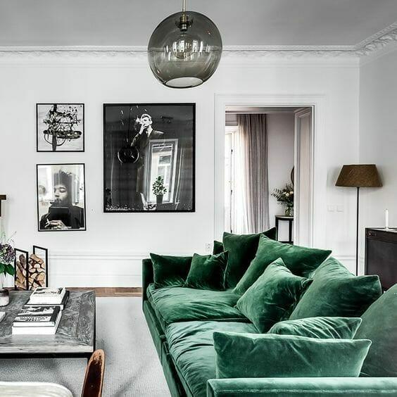 biały salon z welurową kanapą w kolorze butelkowa zieleń i dużymi zdjęciami w czarnej ramie na ścianie trendy 2019