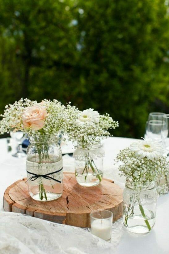 rustykalny stół w ogrodzie obrus i słoiki z kwiatami