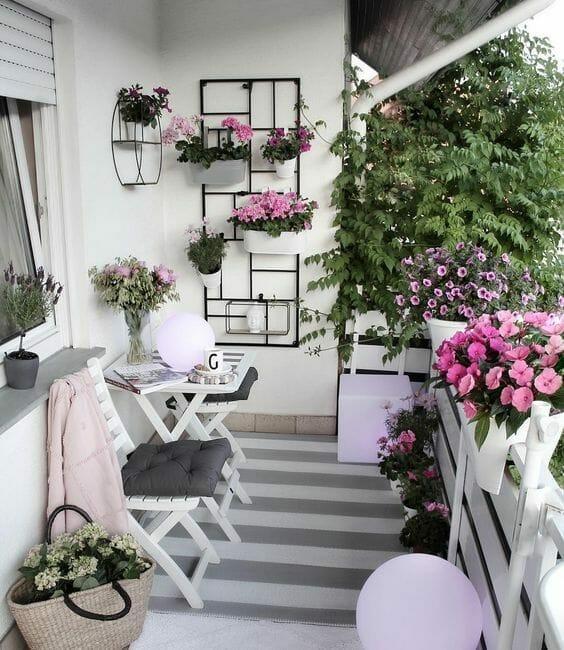 kwiaty na balkonie petunie i bratki, szaro-biały dywan, biały stolik z krzesłami