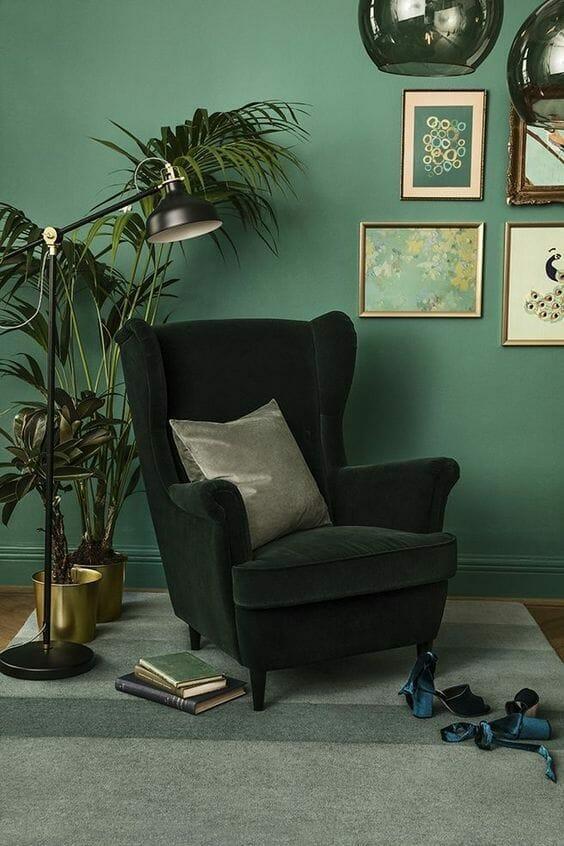 fotel i ściana w kolorze butelkowa zieleń z obrazami na ścianach