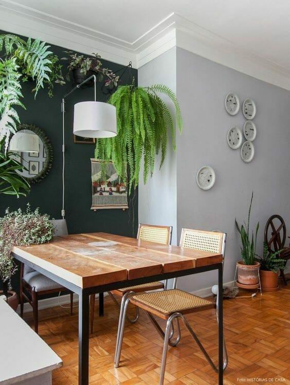 ściana pomalowana na butelkową zieleń w jadalni w okolicy szarych ścian z drewnianym stołem i wiszącą paprocią