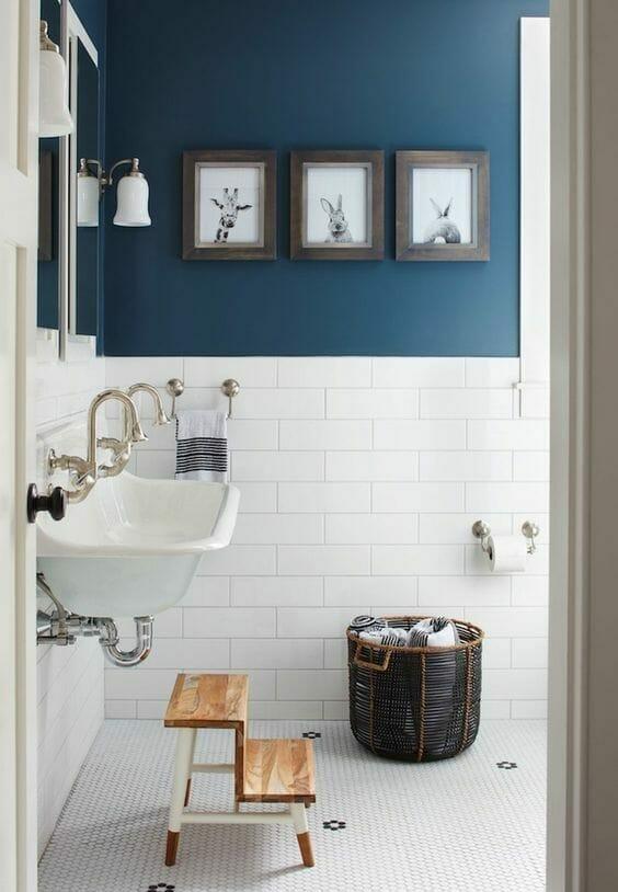 łazienka z białymi kafelkami i niebieskimi ścianami i wiklinowym koszem