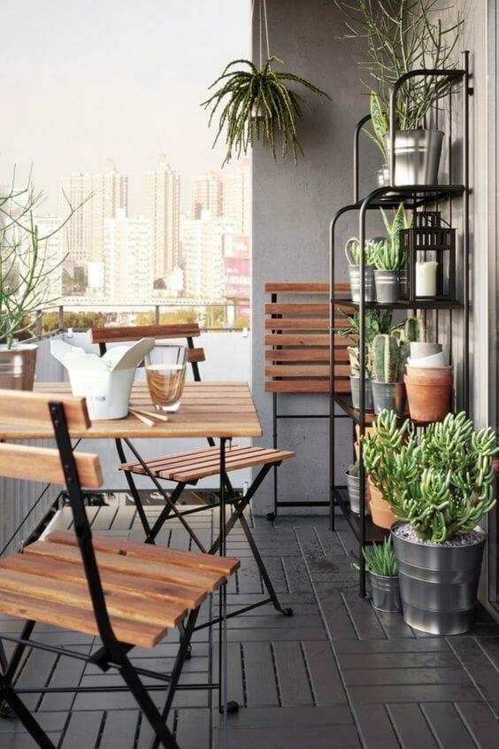 ciemny balkon z kwiatami, krzesłami i stolikiem
