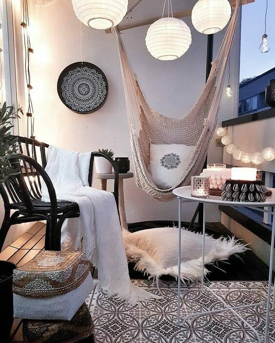 balkon w bloku z fotelem, poduszkami, kocem i huśtawką, drewniane lampiony