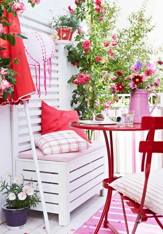 biały balkon z różowymi dodatkami i czerwonym stolikiem
