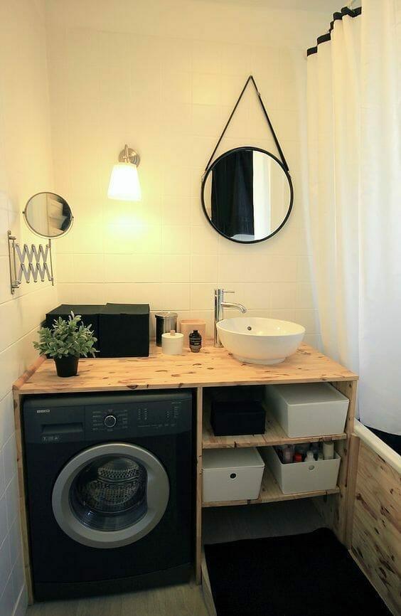 biała łazienka z drewnianym blatem pod umywalką i lustrem w czarnej oprawie