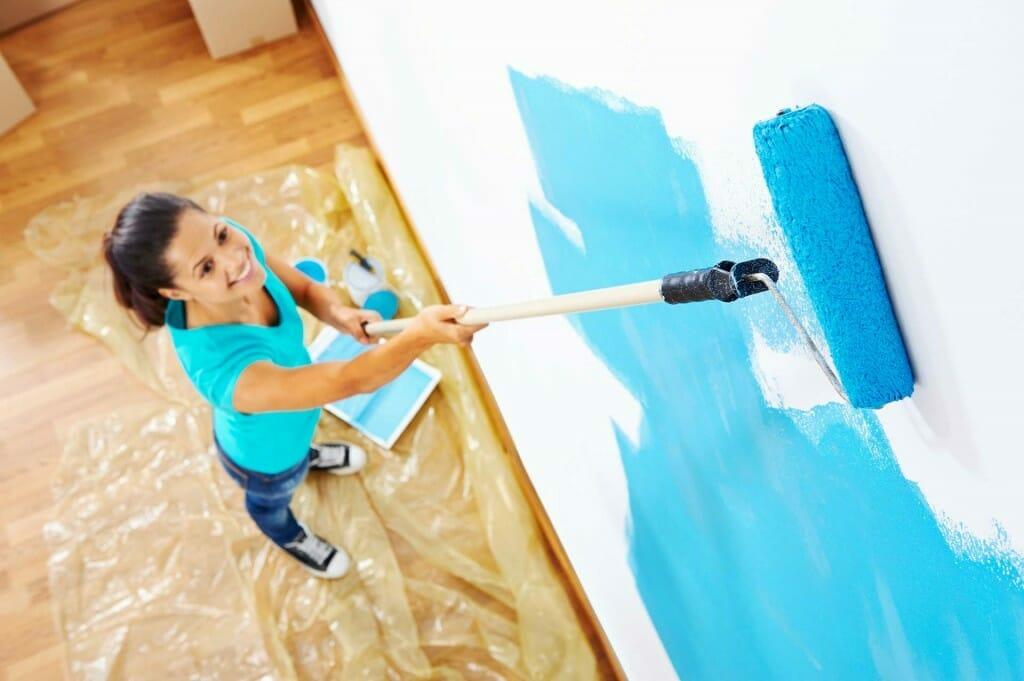 malowanie ścian wałkiem na niebiesko przez kobietę