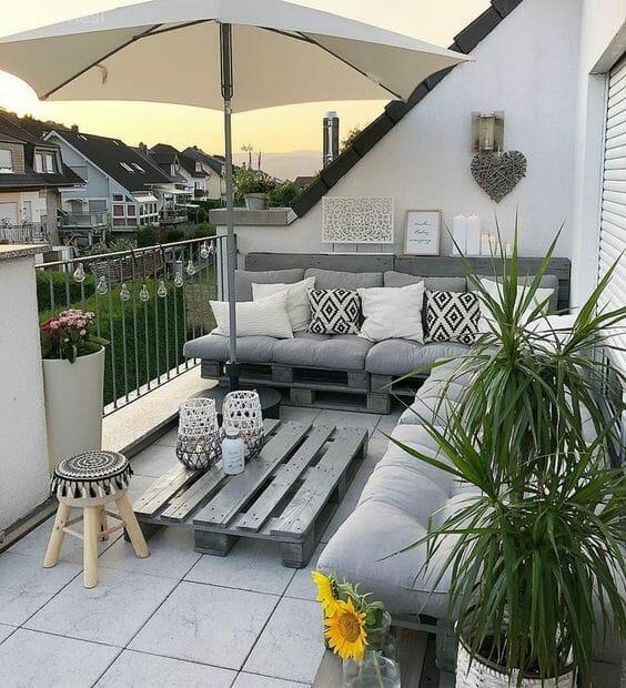 balkon w bloku siedzisko z palet dracena parasol
