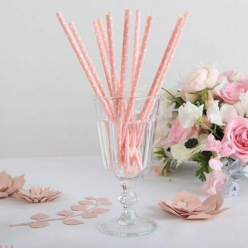 różowe papierowe słomki w białe kropki stojące w kubku na tyle kwiatów