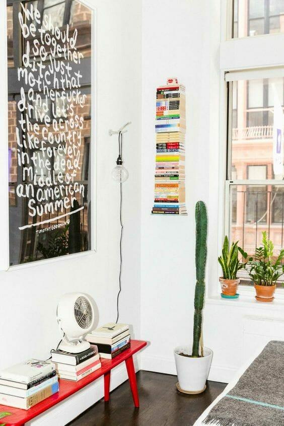 biały salon z kaktusem czerwoną ławką i półka na książki z książki domowa biblioteczka