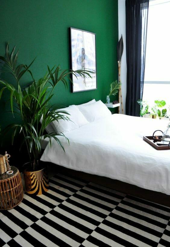 zielona sypialnia z czarno-białym dywanem i łóżkiem z białą pościelą