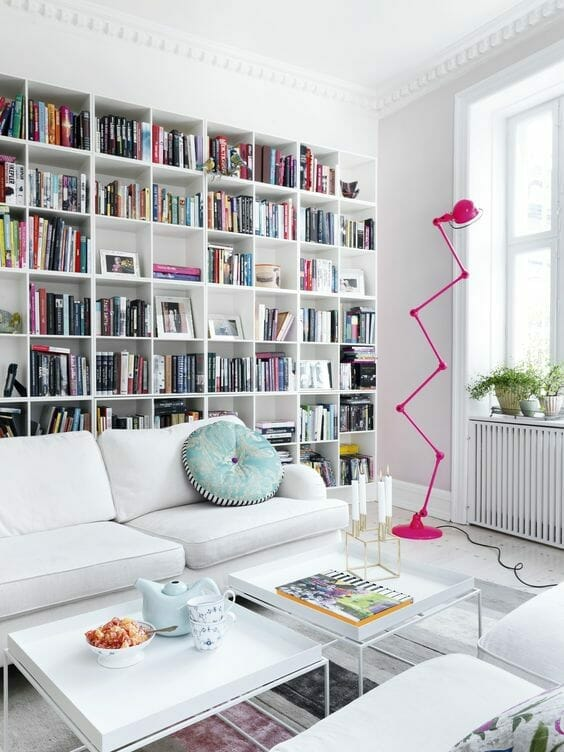 biały salon z kolorowymi akcentami w postaci różowej lampy i domowa biblioteczka