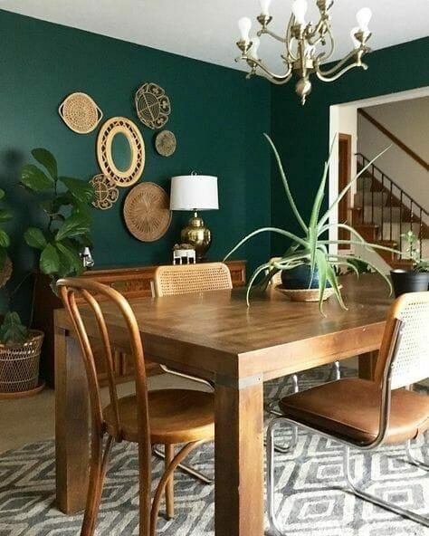 butelkowa zieleń jako kolor ścian w jadalni z wiklinowymi i drewnianymi dodatkami i szarym dywanem