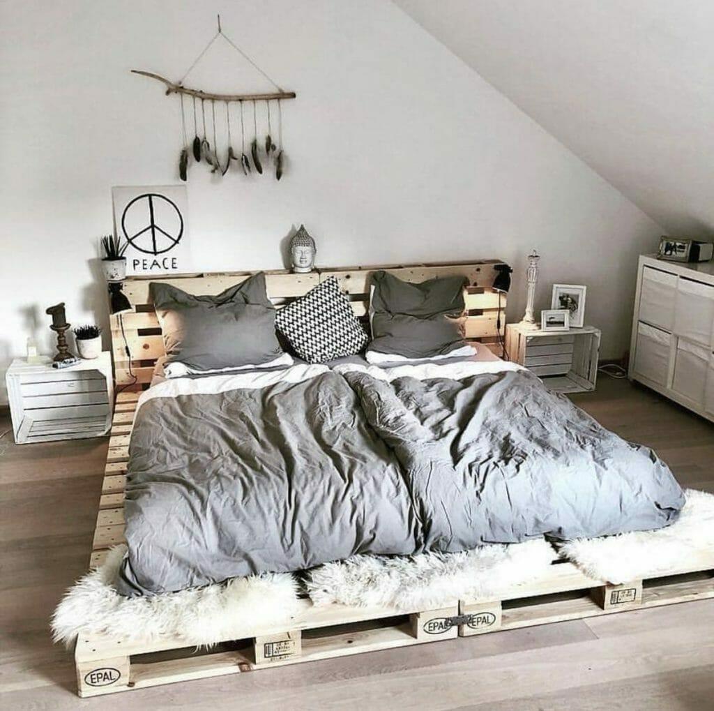 łóżko z palet z szarą pościelą i dodatkami boho