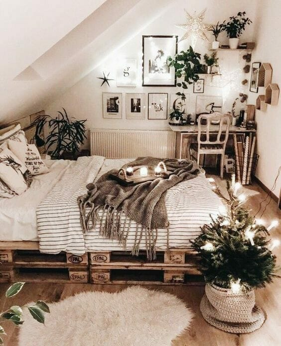 łóżko z palet w sypialni z dużą ilością kwiatów i tekstyliów
