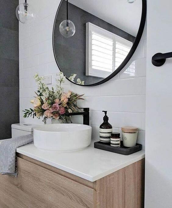 Mała łazienka w bloku okrągłe lustro białe płytki czarna bateria