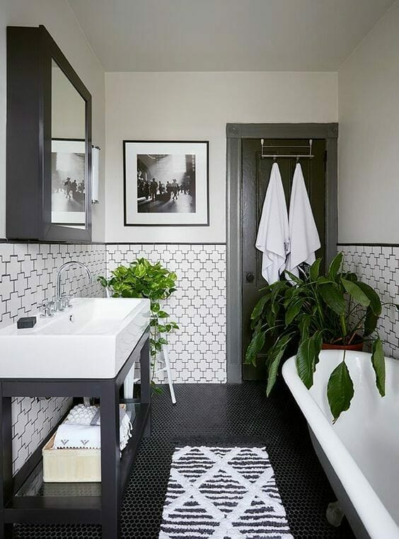 biała łazienka z czarnymi dodatkami i kwiaty do łazienki