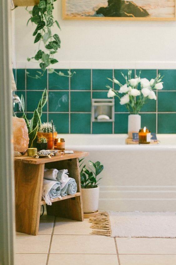 kwiaty doniczkowe w łazience, kafelki w kolorze morskim i białym, palące się kadzidło na drewnianym stołku przy wannie