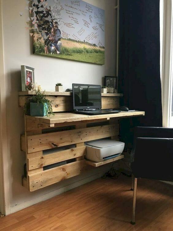 postaci biurka zawieszonego na ścianie z laptopem i roślinami