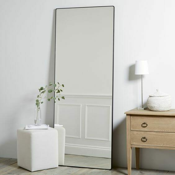 biały przedpokój z prostokątnym lustrem z czarną metalową ramą, meble do przedpokoju w postaci białej pufy i drewnianej szafki