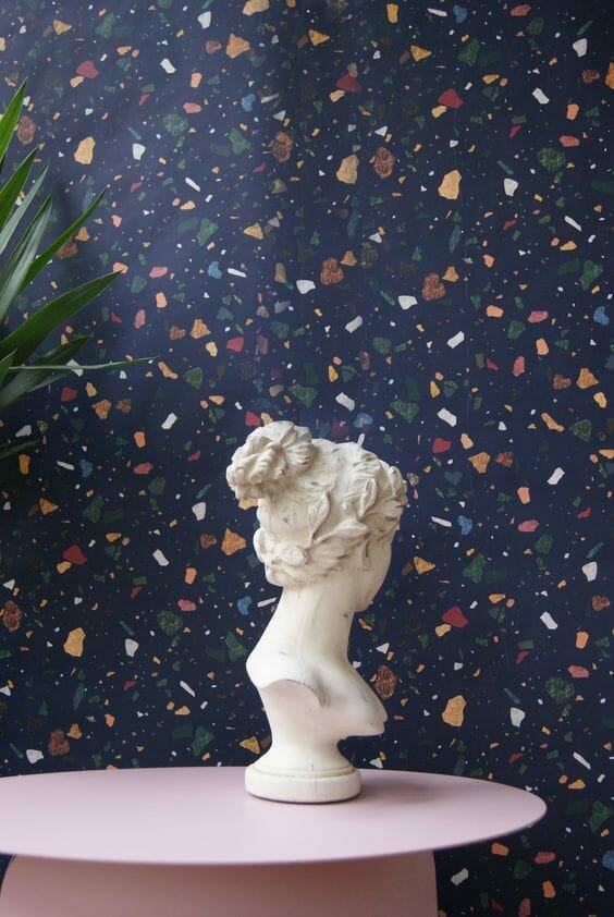 białe popiersie na granatowym tle lastriko z kolorowymi kamieniami stojące na różowym stole