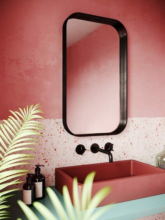 różowa nowoczesna łazienka z lustrem z czarną ramą i czarną baterią