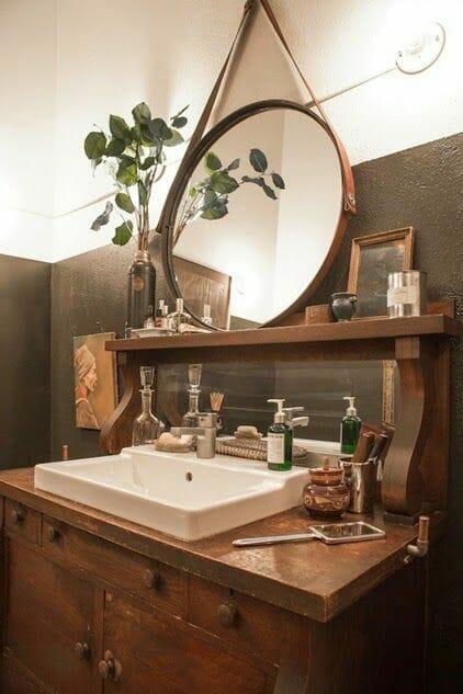 łazienka vintage, stare meble w łazience, czarne ściany w łazience, okrągłe lustro w drewnianej ramie