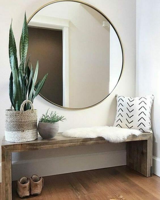 przedpokój beżowy z okrągłym lustrem i drewnianą ławką i roślinami