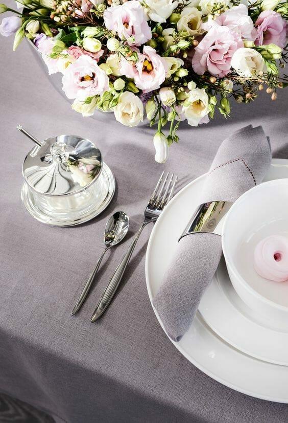nakrycie stołu w kolorze szarym ze srebrnymi dodatkami i białym talerzem