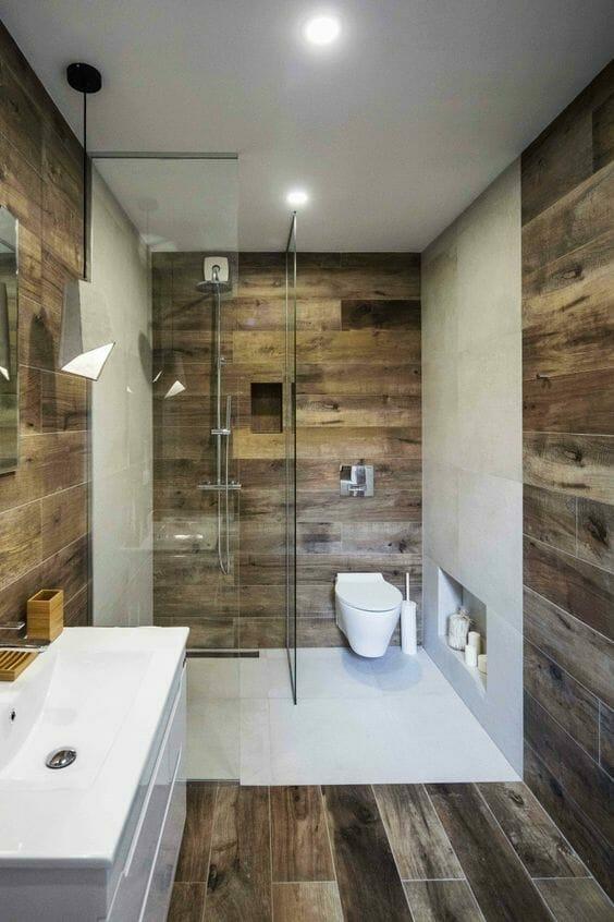 łazienkach w przygaszonych płytkach drewnopodobnych z białymi wstawkami z kamienia i szklanymi szybami prysznicowymi