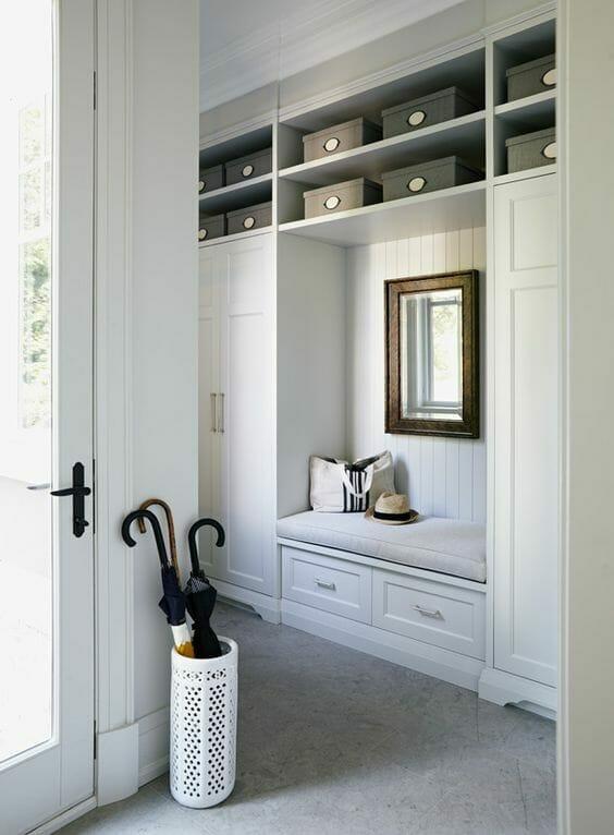 biały stojak na parasole lustro w ciemnej ramie beżowe i szare pudełka białe ściany