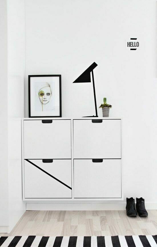 biały geometryczny z grafiką w czarnej ramce i czarną lampą z dywanem w czarno-białe pasy i jasnymi panelami