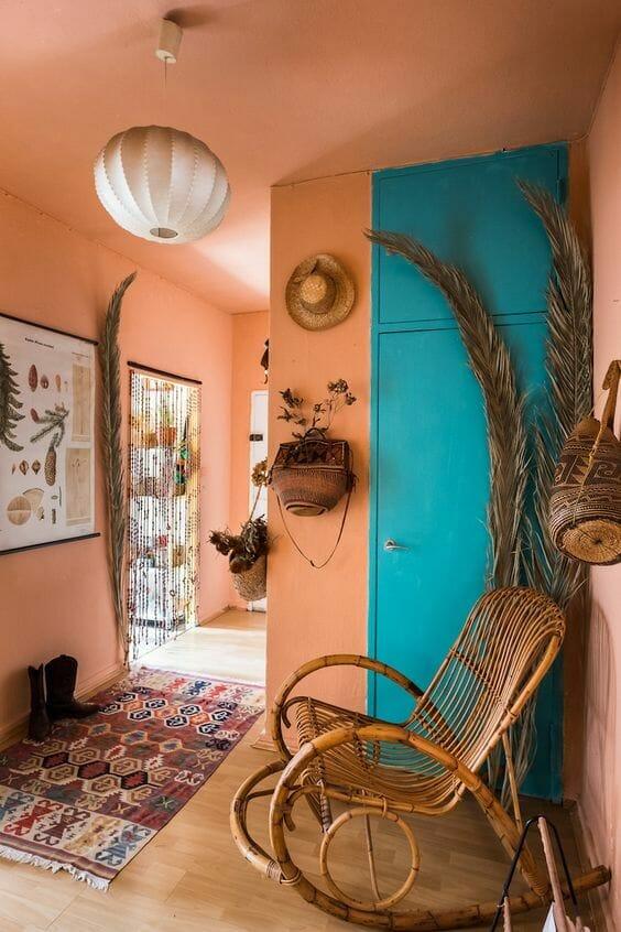 przedpokój koralowy z niebieskimi drzwiami i wiklinowym fotelem i dywanem w etniczne wzory