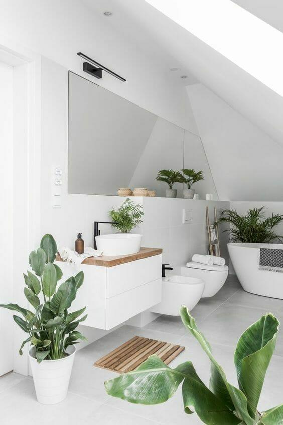 biała łazienka z ukosem z dużą ilością roślin doniczkowych i drewnianymi akcentami