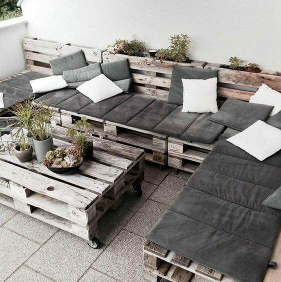 szlifowane palety na balkon w stylu rustykalnym z szarymi poduszkami i roślinami w doniczkach na stoliku na kółkach