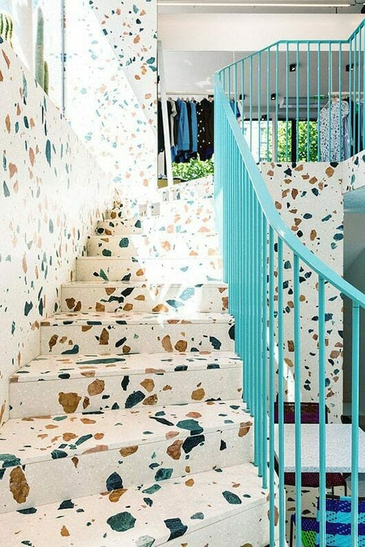 białe lastryko na schodach z kontrastującymi kamieniami i niebieską poręczą