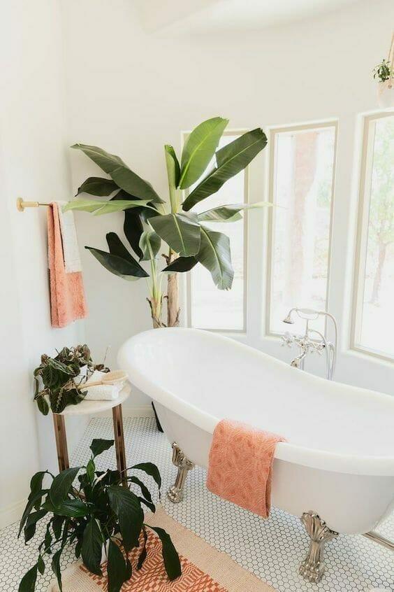 jasna łazienka w kolorze białym z koralowymi dodatkami i rośliny do łazienki, wolnostojąca wanna na srebrnych nóżkach