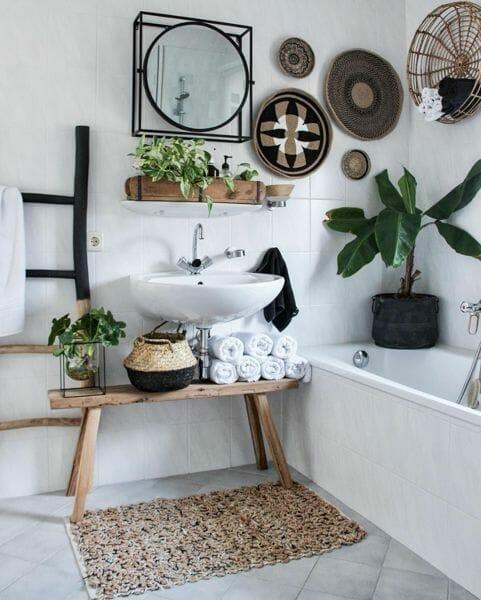 rośliny w łazience w jutowych donicach i okrągłymi boho dodatkami na ścianach wraz z drewnianą drabiną i ławeczką