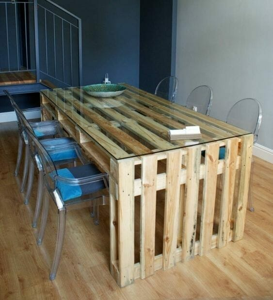 meble z palet w postaci stołu jadalnianego wraz z plastikowymi przezroczystymi krzesłami