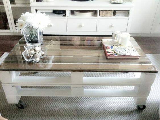 stolik z palet w kolorze białym z dodatkami w postaci kwiatów, świeczek i książek