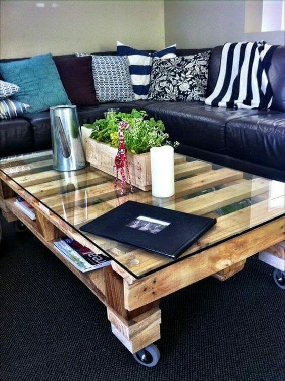 meble z palet w postaci stolika i czarnej skórzanej sofy z poduszkami