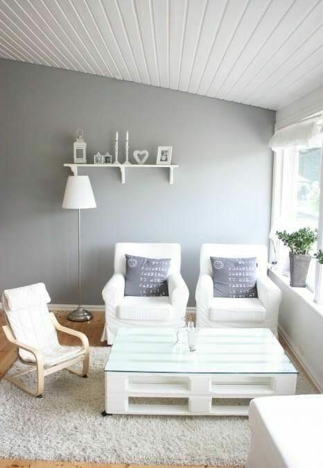 meble z palet w postaci białego stolika w szarym pokoju i białych foteli