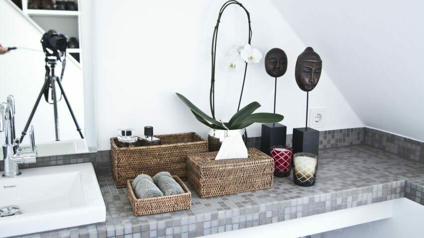 kwiaty do łazienki w postaci białego storczyka stojącego na szarym blacie obok figurka buddy