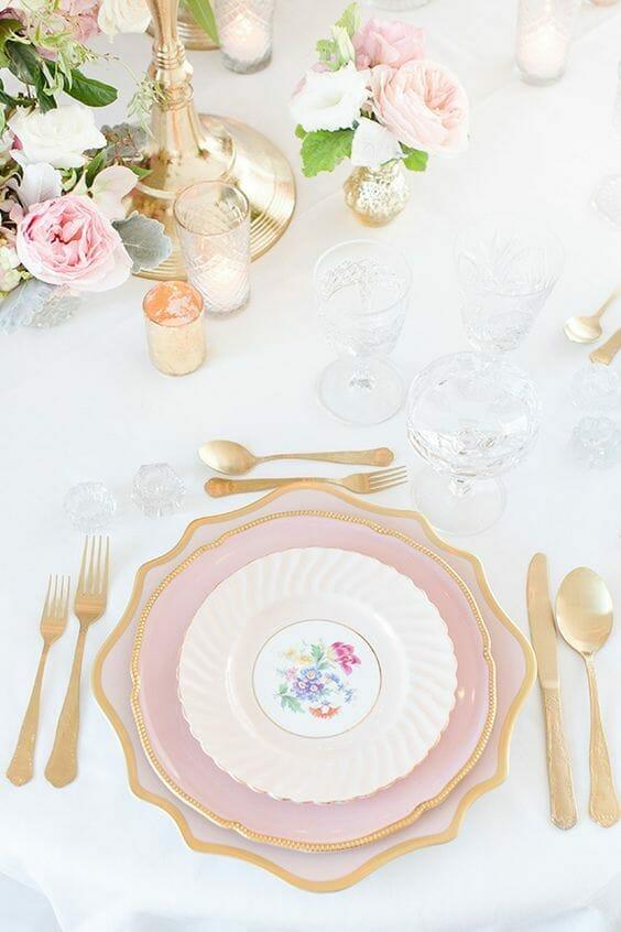 nakrycie stołu ze złotymi sztućcami i różowym talerzem na białym obrusie z kryształowymi kieliszkami zasady savoir vivre