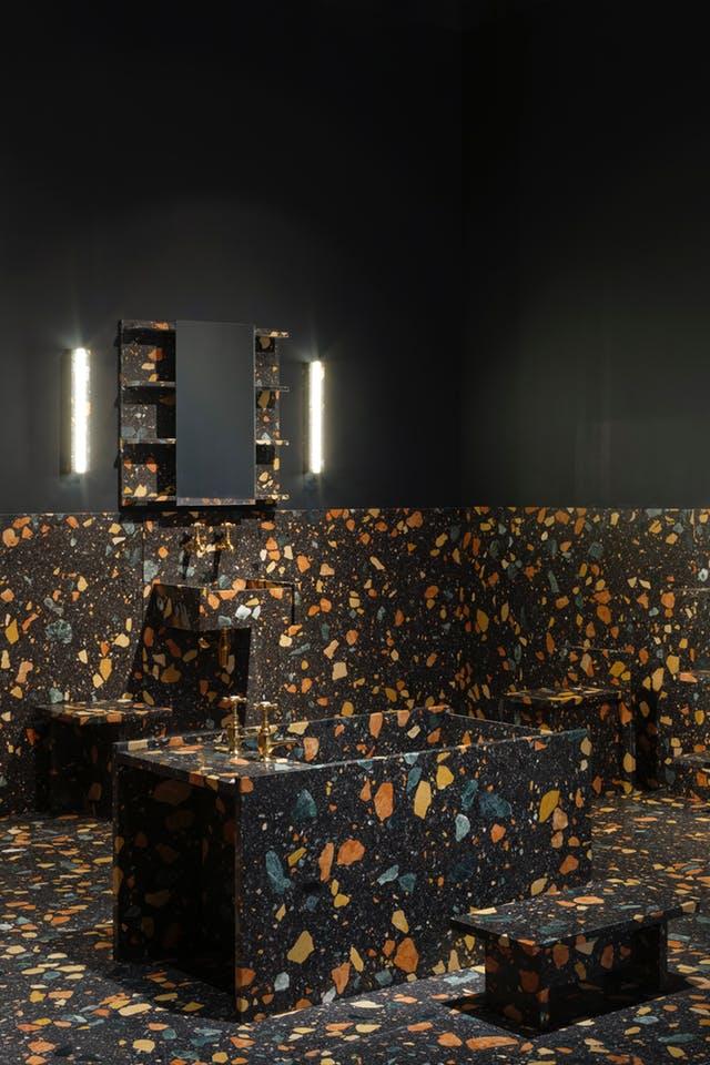 łazienka w kolorze czerni z czarnym lastryko z kolorowymi kamieniami z wanną na środku