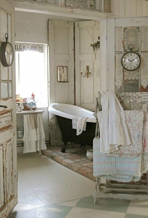 łazienka w stylu shabby chic drewno bielone postarzane drzwi metalowy zegar wolnostojąca wanna na nóżkach