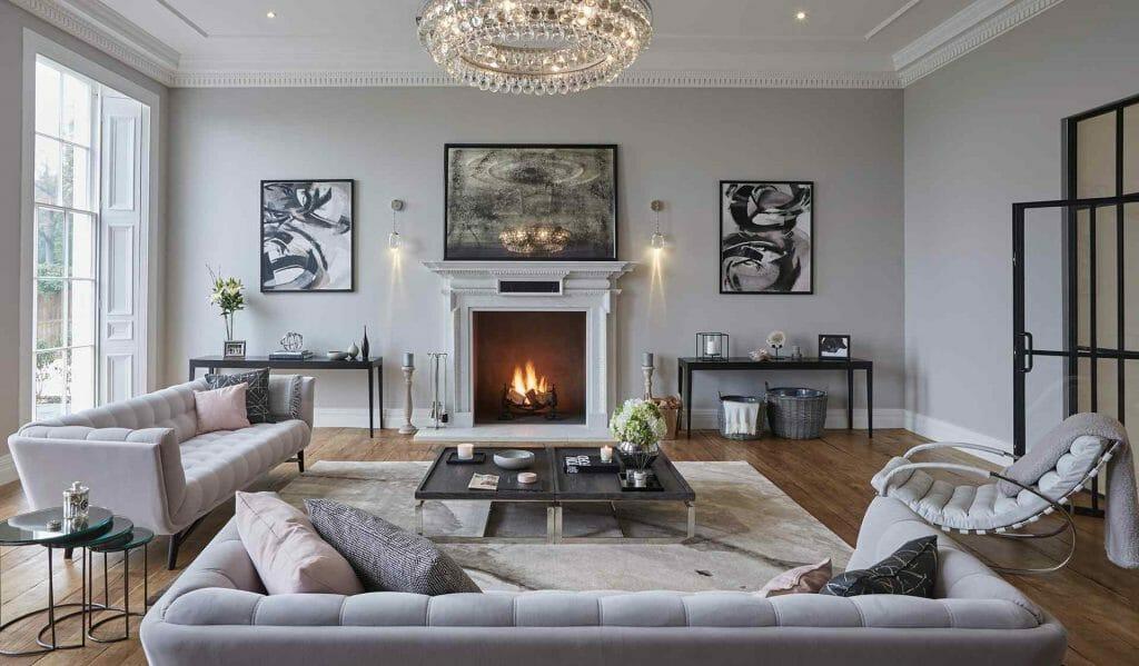 szare ściany salonu w stylu glamour z kryształowym żyrandolem, kominkiem w centrum i szarymi sofami