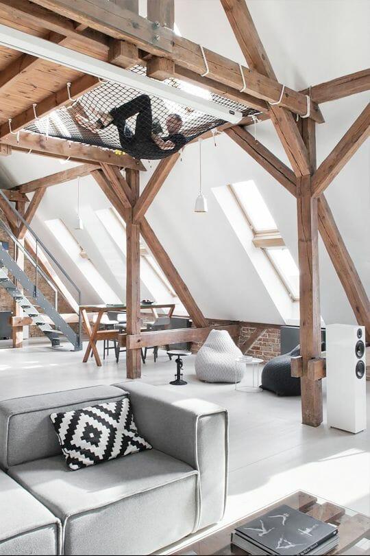 adaptacja poddasza drewniane belki, białe ściany i szare meble