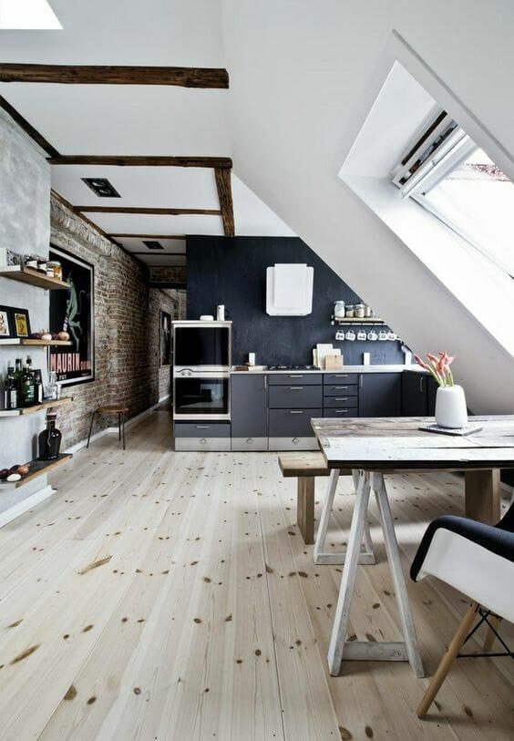 adaptacja poddasza na kuchnię i salon z drewnianą podłogą i biało-szarymi ścianami, ceglastą ścianą w przedpokoju i drewnianymi belkami
