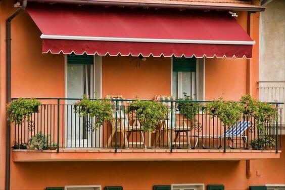 czerwona markiza balkonowa na pomarańczowej ścianie jak osłonić balkon